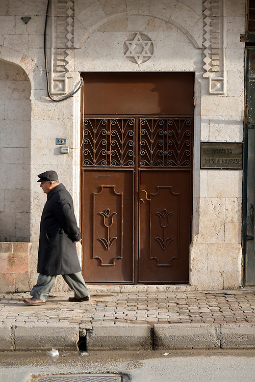 A Turkish man walks past the entrance to the Jewish synagogue in Antakya (Hatay), Turkey. In the ancient world Antakya, then called Antioch, had a thriving Jewish community. Today that number has dwindled to a few dozen.