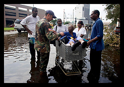 1st Sept, 2005. Mass evacuation of New Orleans begins. A lady arrives in a shopping trolley hoping to be evacuated on the busses only to be turned away having not gone through the official channels.