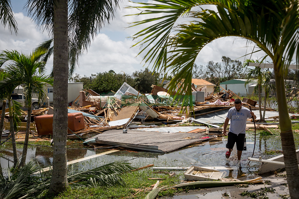 September 11, 2017 - Collier County, Florida, U.S. - RAMIRO GUTIERREZ wades through floodwaters in front of the remnants of a decimated home following Hurricane Irma in southern Collier County on Monday. Hurricane Irma swept through south Florida leaving behind a trail of debris, flooding and power outages. (Credit Image: © Loren Elliott/Tampa Bay Times via ZUMA Wire)