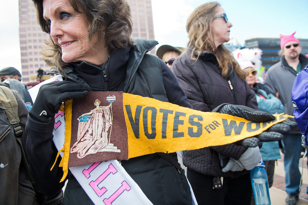 mkb012117e/metro/Marla Brose<br /> Patience Skarsgard holds her grandmother's pennant from when she fought for women's voting rights as a suffragette about 100 years ago, during the Albuquerque Women's Rally, a sister rally of the Women's March on Washington, Saturday, Jan. 21, 2017, in Albuquerque, N.M. The women's rallies and marches through the country and around the world are in response to the inauguration of President Trump. The rally in Albuquerque, which included speakers, singers, poets, dancers and drummers was formed on the idea that &quot;women's rights are human rights,&quot; according to a press release from rally organizers. (Marla Brose/Albuquerque Journal)
