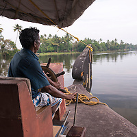 A man pilots a houseboat down a waterway surrounding Kochi in India.