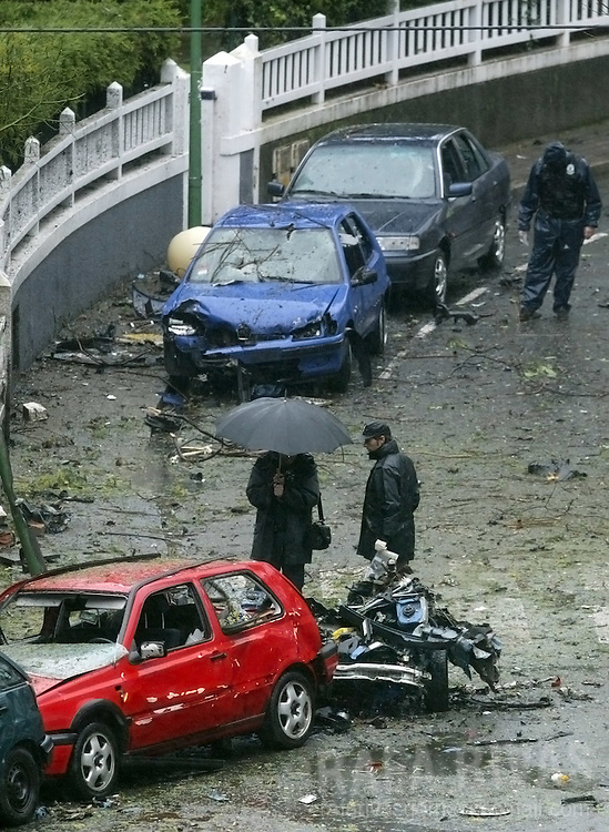 Masked Basque regional policemen examine the rests of a car bomb that exploded 18 January 2005 at Getxo in the Basque country, with armed Basque separatist group ETA claiming responsibility. PHOTO RAFA RIVAS