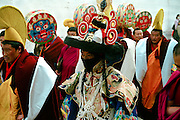 "A costumed dancer surrrouned by high rank monks and Mahakala drums players  is walking in the streets of the monastery of Labrang to join the Cham (tib:dance of the spirits), here: the so-caled ""Black hat dance"". Xiahe, Gansu (Amdo),China."