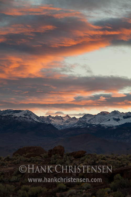 The sun lights stormy clounds as sets behind the eastern Sierra range