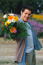 Young man outdoors holding a bouquet of mixed flowers