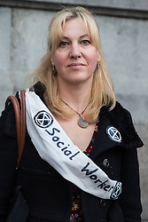 London, UK. 17 October, 2019. A social worker from Extinction Rebellion prepares to defy the Metropolitan Police ban on Autumn Uprising protests under Section 14 of the Public Order Act 1986 by attending an XR Professionals assembly in Trafalgar Square. Activists addressed the assembly about the impact of climate change on their work.