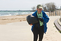 "Saturday, April 22nd, 2017 was Earth Day and the Jackson Park Advisory Council stepped up with various projects around the neighborhood.<br /> <br /> 2588 – President of the Jackson Park Advisory Council, Louise Mcurry carries away garbage at the 57th Street Beach.<br /> <br /> Please 'Like' ""Spencer Bibbs Photography"" on Facebook.<br /> <br /> All rights to this photo are owned by Spencer Bibbs of Spencer Bibbs Photography and may only be used in any way shape or form, whole or in part with written permission by the owner of the photo, Spencer Bibbs.<br /> <br /> For all of your photography needs, please contact Spencer Bibbs at 773-895-4744. I can also be reached in the following ways:<br /> <br /> Website – www.spbdigitalconcepts.photoshelter.com<br /> <br /> Text - Text ""Spencer Bibbs"" to 72727<br /> <br /> Email – spencerbibbsphotography@yahoo.com"