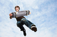 Man jumping holding skateboard in mid-air low angle view