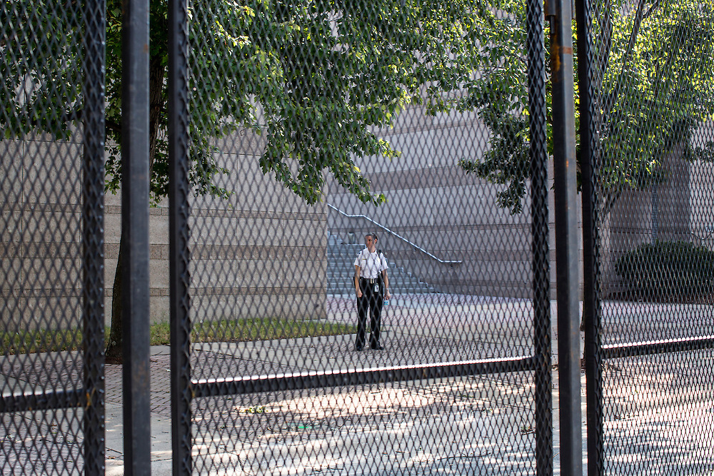 A security guard outside the county courthouse is seen through the security fence for the Democratic National Convention on Monday, September 3, 2012 in Charlotte, NC.
