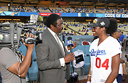 Jun 13, 2018; Los Angeles, CA, USA; KCBS Los Angeles sports television anchor Jim Hill (left) interviews Kendall Ellis (4) before a MLB game between the Texas Rangers and the Los Angeles Dodgers at Dodger Stadium. Ellis ran the anchor leg on the Southern California Trojans women's 4 x 400m relay that won the NCAA title in the final even to win  the national team title.