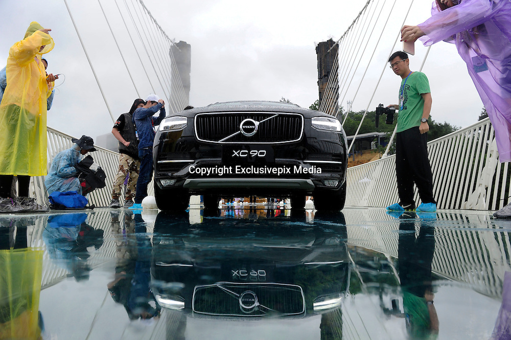 ZHANGJIAJIE, CHINA - JUNE 25:<br /> <br />  A car drives over glass-bottomed bridge for a safety test at Zhangjiajie Grand Canyon on June 25, 2016 in Zhangjiajie, Hunan Province of China. World\'s tallest and longest glass-bottomed bridge has been completed and took a global broadcast through television and internet medias to show its safety. More than thirty citizens and visitors thumped the bridge with hammer in the test event. &copy;Exclusivepix Media