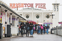 © Licensed to London News Pictures. 10/03/2018. Brighton, UK. Members of the public shelter from the rain as they visit the Brighton Palace Pier in Brighton and Hove.  Photo credit: Hugo Michiels/LNP