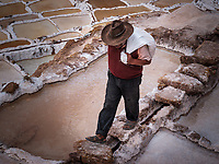 MARAS, PERU - CIRCA SEPTEMBER 2019:  Worker carrying a bags at the Marasal salt mines near the village of Maras in the Cusco region known as Sacred Valley