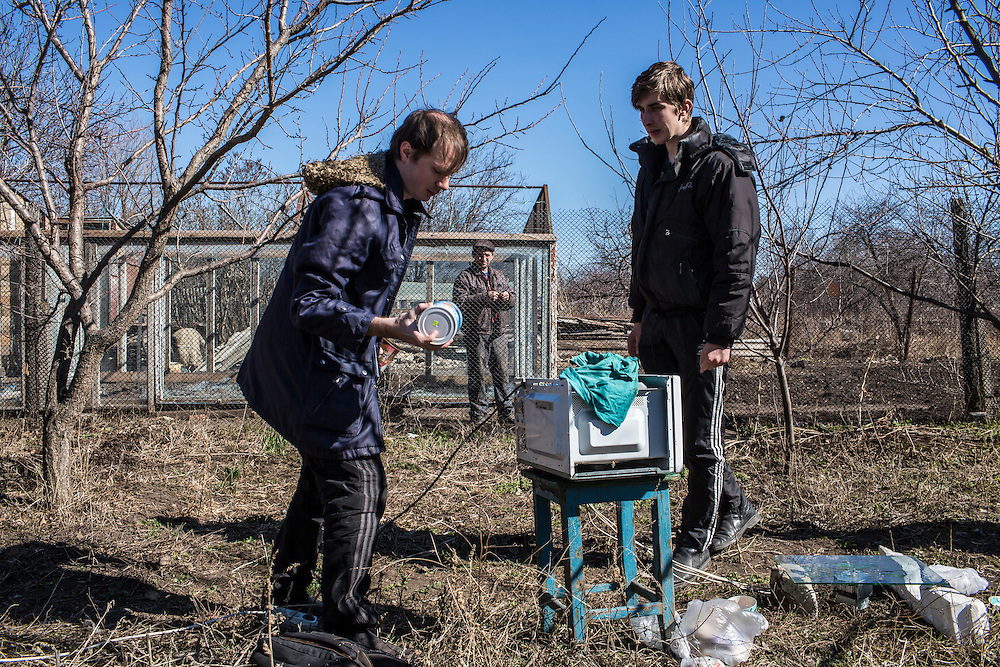 LUHANSK, UKRAINE - MARCH 16, 2015: Aleksandr Kryukov, left, and Pavel Pavlov prepare materials for scientific experiements involving microwaves in the yard of the house where Kryukov lives with his grandmother as a neighbor watches in Luhansk, Ukraine. The two have created a series of popular YouTube videos involving scientific experiements. CREDIT: Brendan Hoffman for The New York Times