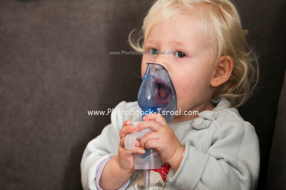 Baby uses an inhalation mask by herself