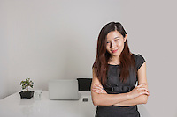Portrait of confident young businesswoman standing arms crossed in office