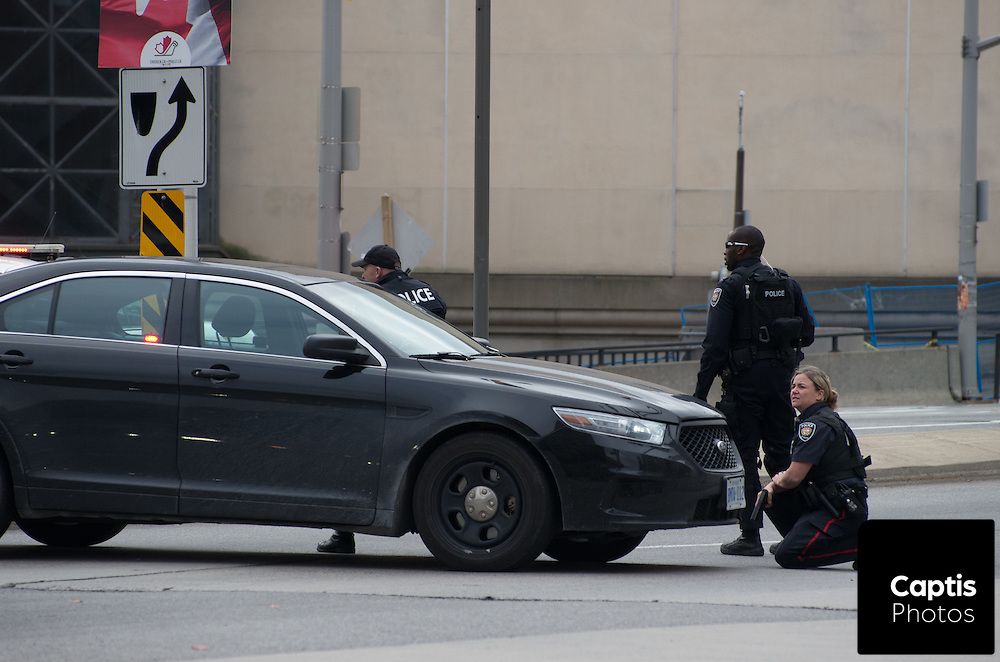 Police take cover behind a car while other officers enter the Rideau Centre. The Rideau Centre was placed under lock down following the shooting of Cpl. Nathan Cirillo at the National War Memorial. October 22, 2014.