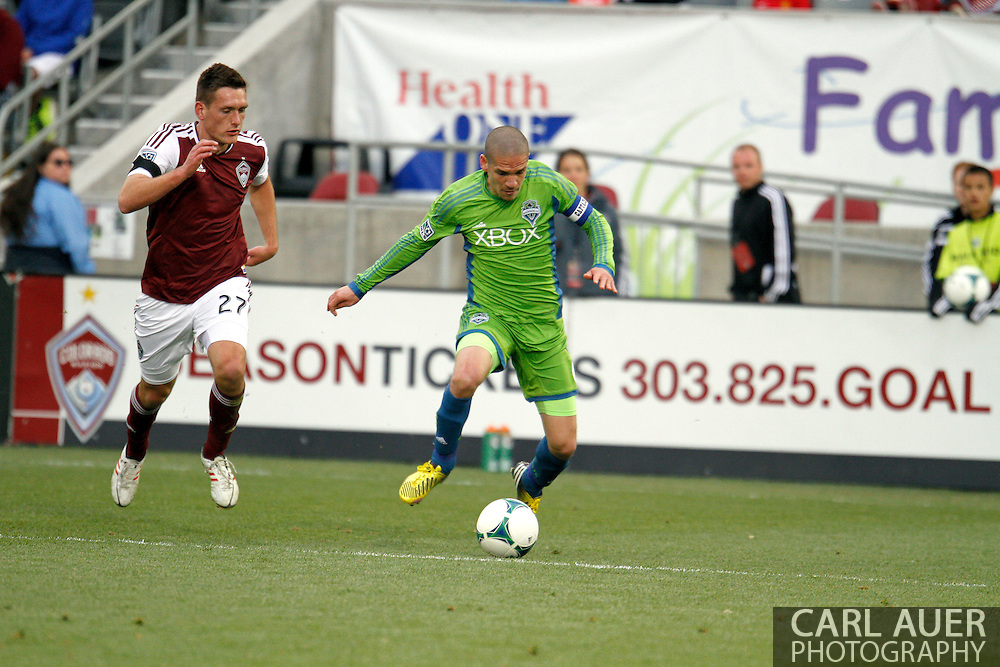April 20th, 2013 Commerce City, CO - Seattle Sounders FC midfielder Osvaldo Alonso (6) sets to cross the ball past the defense by Colorado Rapids midfielder Shane O'Neill (27) to get to the ball first in the second half of the MLS match between the Seattle Sounders FC and the Colorado Rapids at Dick's Sporting Goods Park in Commerce City, CO