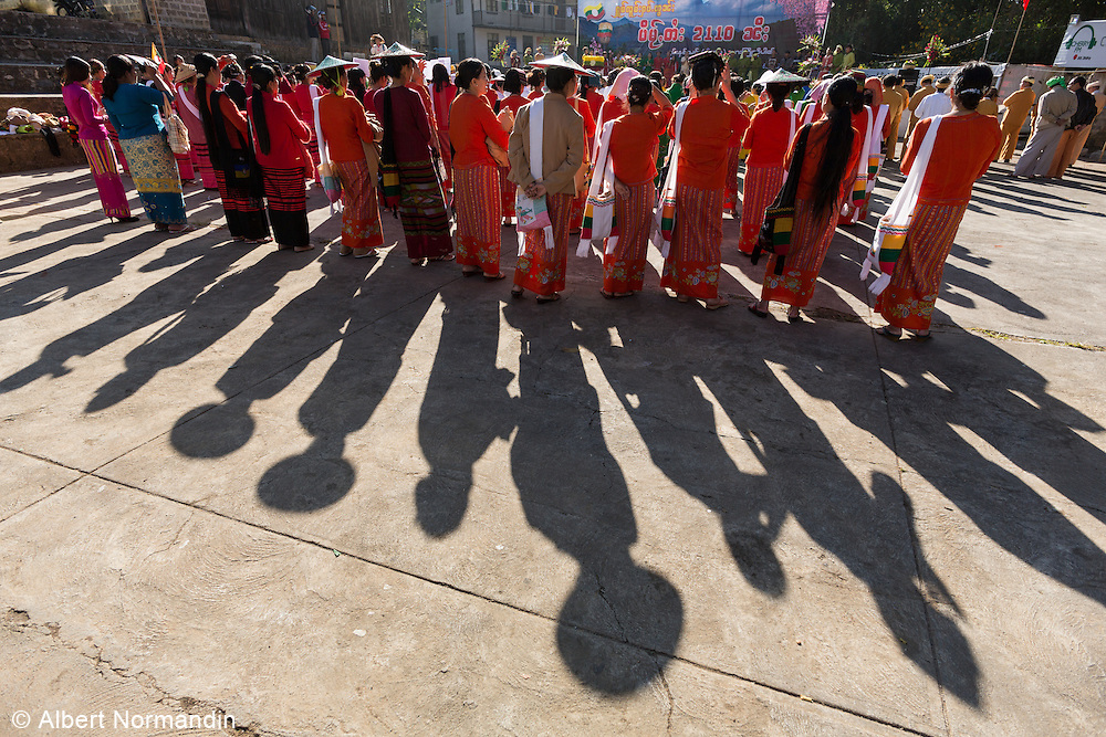Woman in traditional dress and big hats with long shadows at Pa O Festival, Taunggyi