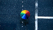 Under the cover of a rainbow umbrella a pedestrian walks across Princes Street in Edinburgh, Scotland.  This image was taken from the top of Scott Monument.