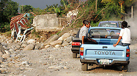 Diverted traffic makes its way through a rural, coastal area. Traffic was stymied on a major coastal route for weeks until road crews could construct a makeshift road in place of one that was washed out when the swollen river overran its banks, altered the area's landscape and destroyed several houses in early October. Torrential rains associated with Hurricane Stan inundated parts of Central America in early October, causing flooding, mudslides and death across western Guatemala. Many areas have been cut off due to washed out roads and bridges.<br />