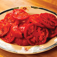 This plate of fresh tomatoes represents a summer tradition. Recipe: 2 slices fresh white bread slathered with real mayonnaise topped with 2 tomato slices, add salt and pepper.