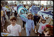Kids and adults march in Earth Day parade with marine animal cut-outs; Forest Park, St. Louis Missouri