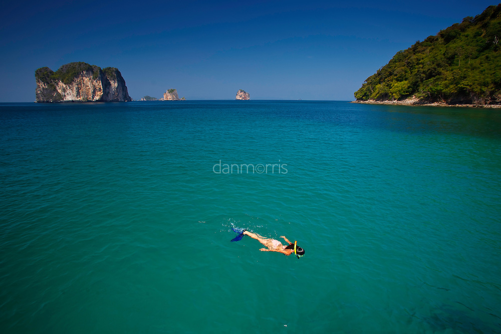 Woman snorkeling in turquoise waters near Chicken Island (Koh Gai), Krabi Thailand