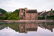 Cothay Manor reflected in a pond at sunrise. Greenham, Wellington, Somerset, UK