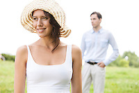 Thoughtful young woman smiling while man standing in background at park