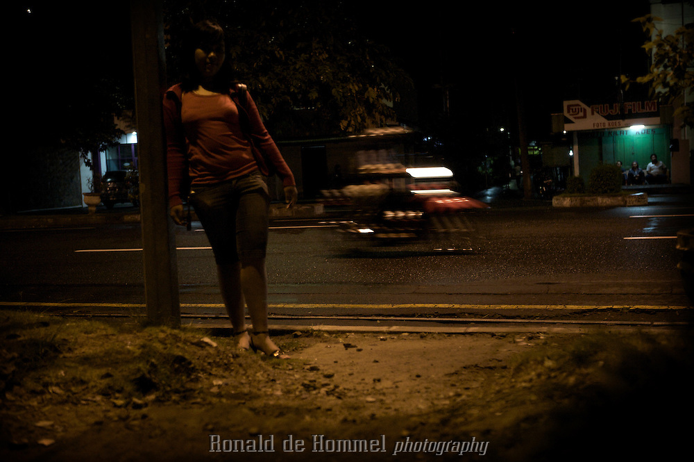 2009-03-05 Solo, Indonesia..A young prostitute late at night walking the streets in central Solo. ..Child prostitution is a growing problem in Indonesia. Forced by poverty or lured by the luxury of modern life many girls end up in prostitution. Many girls make the first step just to be able to buy a mobile phone or to go out in an expensive nightclub. .Shopping malls are favorite hangouts to pick up clients. Schoolgirls skip classes and hang around, still in uniform, hoping for a client. Their pimps may be classmates of the same age. Regular customers keep in contact through SMS, Facebook of Friendster. Others hang out in nightclubs or on the street. Some clubs keep a few girls for their customers. They're kept as prisoners and are not allowed to leave the premises alone. ..Kakak a local women's organization in Java approaches girls and tries to educate them about their rights and offers them alternatives like vocational training. Terre des Hommes Netherlands is campaigning against child exploitation and supports Kakak..