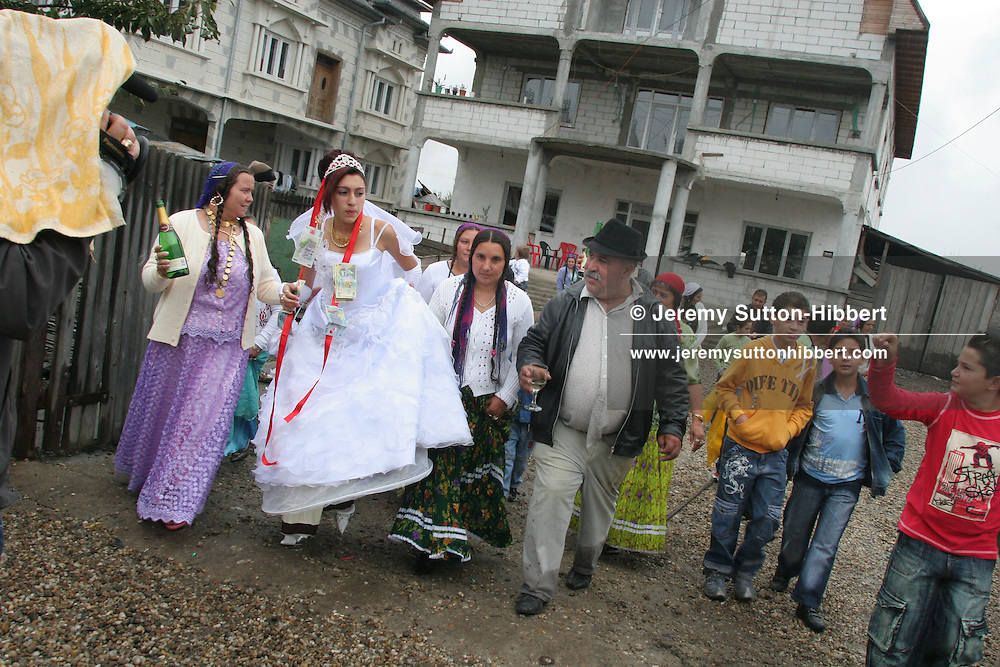 A roma wedding in Sintesti, Romania, on Saturday, Sept. 23rd 2006. Garoafa Mihai (in wedding dress), aged 14, is taken from her family home by her husband-to-be's family,( including father Gogoaie Lulu in black hat, centre) at the beginning of the celebrations of her wedding to 13 year old Florin 'Ciprian' Lulu (in yellow sports top, third from right). Both are Roma (gypsies) from the village of Sintesti, 15 kilometres from Bucharest, Romania. Their partnership was decided by their parents and not through love, and under Romanian law is illegal. The children will neither complete legal paperwork for the wedding, nor visit the local Romanian Orthodox church for a blessing. On her wedding day Garoafa wore approximately 30-40,000 USD of gold Franz Josef coins on her dress, part of the large dowry that she takes with her as she begins her married life. For the guests and for the people of the village another 30,000 USD of pigs were killed to be eaten and given away as presents of food. Another 30,000 USD was spent on famous Roma musicians to come and sing 'manele'  type music at the wedding extolling the wealth and status of their patrons for the weekend in their songs.