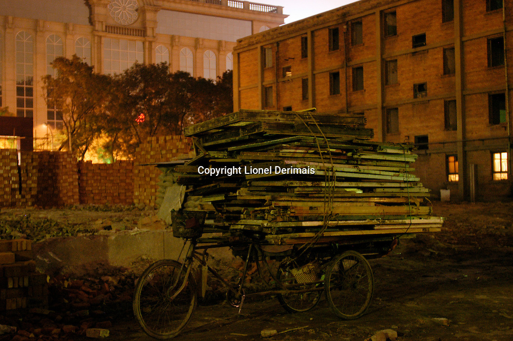 Scrap and salvaged wood piled up on a tricycle taken from window frames and doors as old homes are destroyed in Sanlitun, Beijing, China.