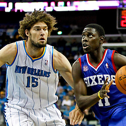 November 7, 2012; New Orleans, LA, USA; Philadelphia 76ers point guard Jrue Holiday (11) drives past New Orleans Hornets center Robin Lopez (15) during the second half of a game at the New Orleans Arena. The 76ers defeated the Hornets 77-62. Mandatory Credit: Derick E. Hingle-US PRESSWIRE