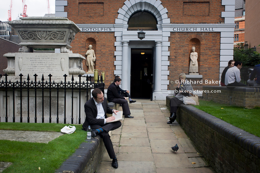 City workers relax during lunchtime outside St Botolph's Church Hall. Originally an infants' school, St Botolph's Church Hall stands in the churchyard of the Church of St Botolph-without-Bishopsgate. The entrance to the hall is flanked by two Coade stone statues of a schoolboy and schoolgirl wearing 19th century costume.