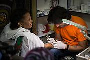 Wassim Razzouk mentre tatua una pellegrina etiope. La sofferenza ed il travaglio del tatuaggio sono per molti un'identificazione nelle pene del Cristo
