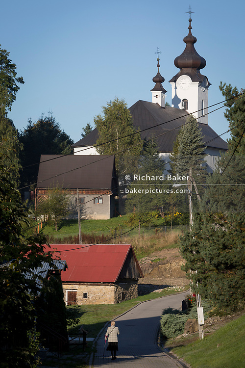 A lady worshipper walks to Sunday Mass at the Greek-Catholic Jana Chrzciciela church, on 21st September 2019, in Jaworki, near Szczawnica, Malopolska, Poland.