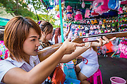 "27 NOVEMBER 2012 - BANGKOK, THAILAND: A Thai school girl takes aim with a pellet rifle at a shooting booth at the Wat Saket Temple Fair in Bangkok. Thailand is facing a rising tide of gun violence and is wrestling with how to curb it. Despite strict gun control laws, more and more guns are showing up in the country. Wat Saket, popularly known as the Golden Mount or ""Phu Khao Thong,"" is one of the most popular and oldest Buddhist temples in Bangkok. It dates to the Ayutthaya period (roughly 1350-1767 AD) and was renovated extensively when the Siamese fled Ayutthaya and established their new capitol in Bangkok. The temple holds an annual fair in November, the week of the full moon. It's one of the most popular temple fairs in Bangkok. The fair draws people from across Bangkok and spills out in the streets around the temple.    PHOTO BY JACK KURTZ"