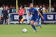 AFC Wimbledon midfielder Scott Wagstaff (7) dribbling with Wycombe Wanderers manager Gareth Ainsworth watching on in the background during the EFL Sky Bet League 1 match between AFC Wimbledon and Wycombe Wanderers at the Cherry Red Records Stadium, Kingston, England on 31 August 2019.