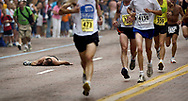 A runner collapses as he approached the finish line in the 10-mile event in the Crim Festival of Races. There were over 7000 competitors in the 29th annual run through the streets of Flint.