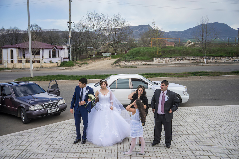 STEPANAKERT, NAGORNO-KARABAKH - APRIL 17: Groom Davit Simonyan, 24, and bride Shogher Hovsepyan, 25, arrive at the Tatik Papik monument to take pictures with family and friends on April 18, 2015 in Stepanakert, Nagorno-Karabakh. Since signing a ceasefire in a war with Azerbaijan in 1994, Nagorno-Karabakh, officially part of Azerbaijan, has functioned as a self-declared independent republic and de facto part of Armenia, with hostilities along the line of contact between Nagorno-Karabakh and Azerbaijan occasionally flaring up and causing casualties. (Photo by Brendan Hoffman/Getty Images) *** Local Caption *** Davit Simonyan;Shogher Hovsepyan