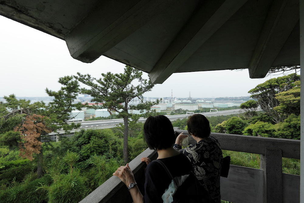 people looking out towards coastal heavy industry landscape