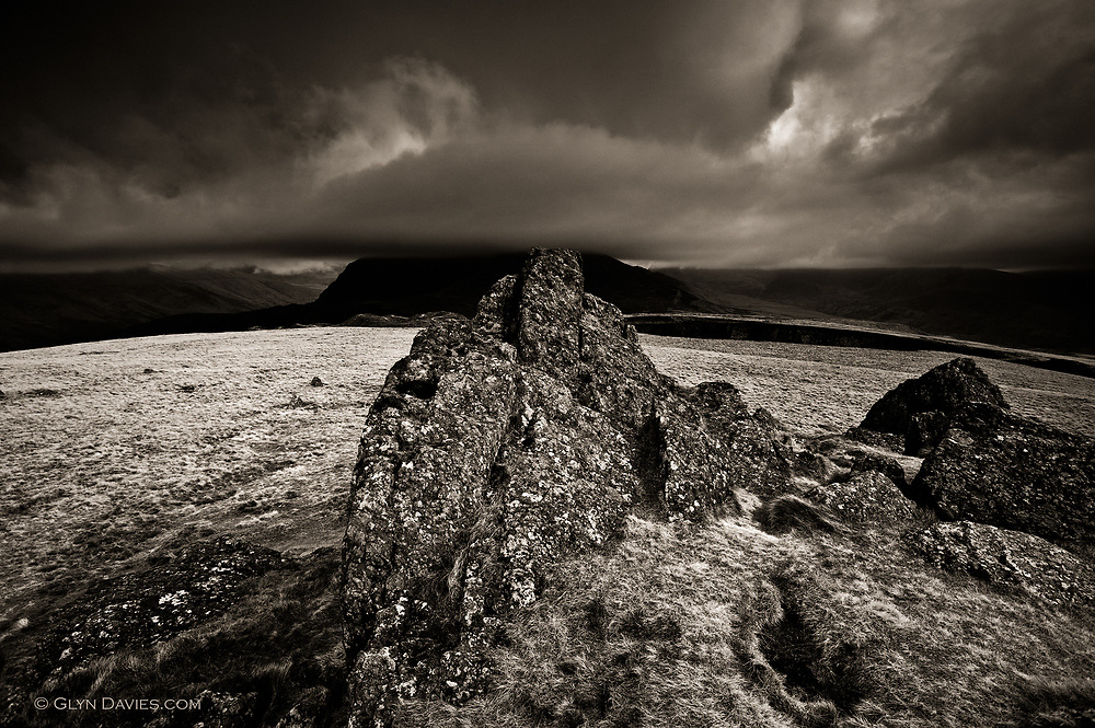 An ominous looking Mynydd Mawr in low cloud and bad weather as seen from the craggy summit of Moel Tryfan above Rhostryfan, Snowdonia, Gwynedd, Wales