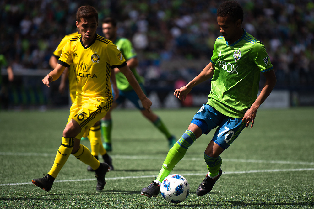 May 05, 2018; Seattle, Washington, US;  Seattle Sounders forward Handwalla Bwana (70) keeps the ball away from Columbus Crew midfielder Hector Jimenez (16) during in action between the Seattle Sounders FC and Columbus Crew at Century Link Field. Photo credit: Rick May - Rick May Photography