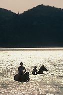 Silhouette of two people riding horses in the sea, Horseshoe Bay, Magnetic Island, Queensland, Australia.