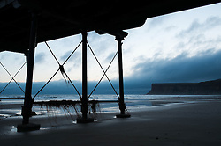 © Licensed to London News Pictures. 10/03/2014<br /> <br /> Saltburn, Cleveland, United Kingdom<br /> <br /> At first light Huntcliff can be seen through the legs of the pier in Saltburn by the Sea in Cleveland.<br /> <br /> Photo credit : Ian Forsyth/LNP