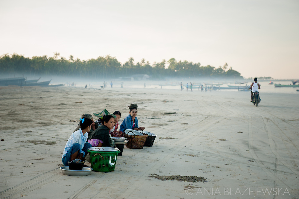 Myanmar, Ngapali. Women wait for their men to come back with a daily catch.<br /> Every single morning all the fisherman from the little village at Ngapali Beach come back home with their night catch. At the beach all the women wait for them and afterwards work with drying and selling fish and other creatures from the sea begins.