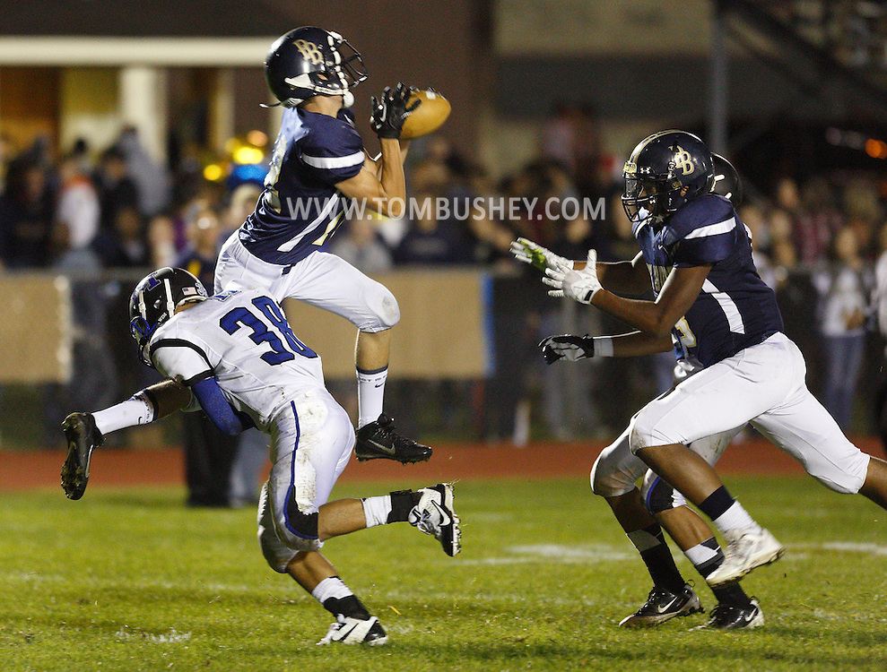 Pine Bush's Artie Econom, left, leaps to catch a touchdown pass as Middletown's Lex Galarza defends during a game in Pine Bush on Friday, Sept. 27, 2013. Pine Bush's Justin Speights (8) and Middletown's Isaiah Reyes, rear, are at right.