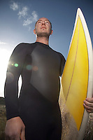 Man holding surfboard standing on beach low angle view