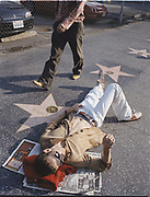 Partial view of one man walking by another man laying down on pavement of the Hollywood walk of fame.